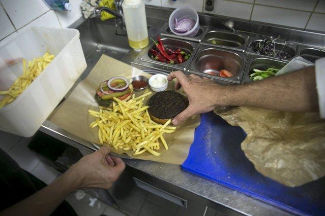 Kitchen staff arrange a plate at Georgian restaurant Nanuchka in Tel Aviv, Israel July 15, 2015. (Photo by Baz Ratner/Reuters)