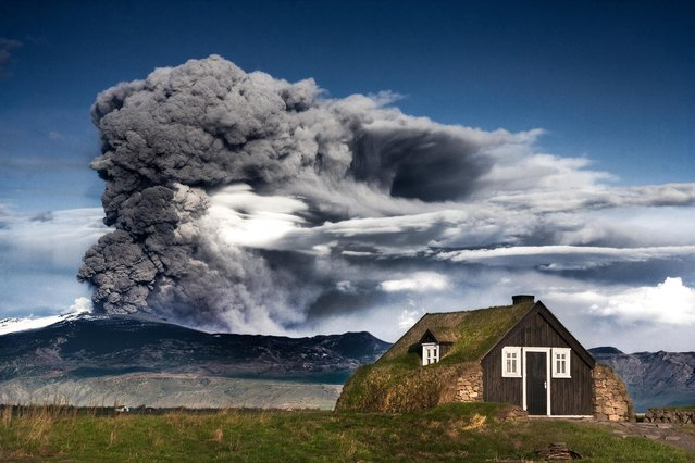 Replica of an old traditional Icelandic house from the 1800 with eruption of Iceland's Eyjafjallajökull volcano, 2013. (Photo by Ingólfur Bjargmundsson/Getty Images)