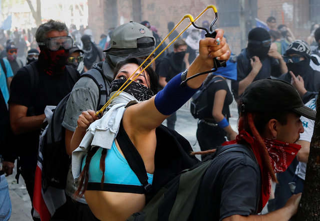 A demonstrator uses a slingshot during a protest against Chile's government in Santiago, Chile, November 14, 2019. (Photo by Jorge Silva/Reuters)