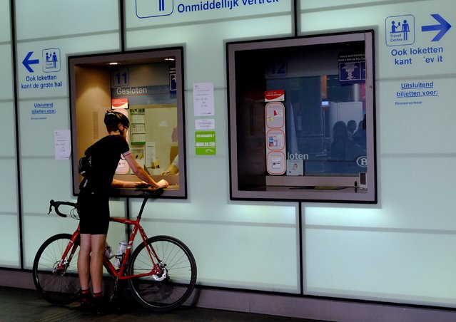 A man with bicycle buys a train ticket at the Antwerp Central station ticket office, Belgium, July 6, 2015. (Photo by Stefano Rellandini/Reuters)