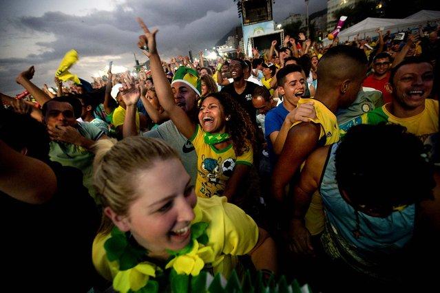 Fans celebrate a goal scored by Brazil in the World Cup opener, during the FIFA Fan Fest on Copacabana beach in Rio de Janeiro. (Photo by Silvia Izquierdo/Associated Press)