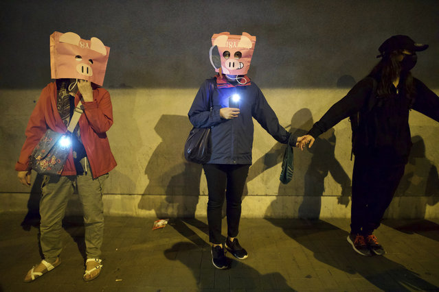 Protesters wear masks as they join hands to form a human chain during a rally in Hong Kong, Saturday, November 30, 2019. (Photo by Ng Han Guan/AP Photo)