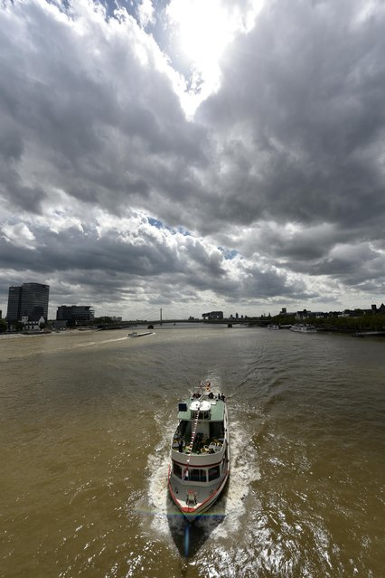 A ship drives on the river Rhine under a cloudy sky on a warm spring Tuesday, May 5, 2015 in Cologne, Germany. (Photo by Martin Meissner/AP Photo)