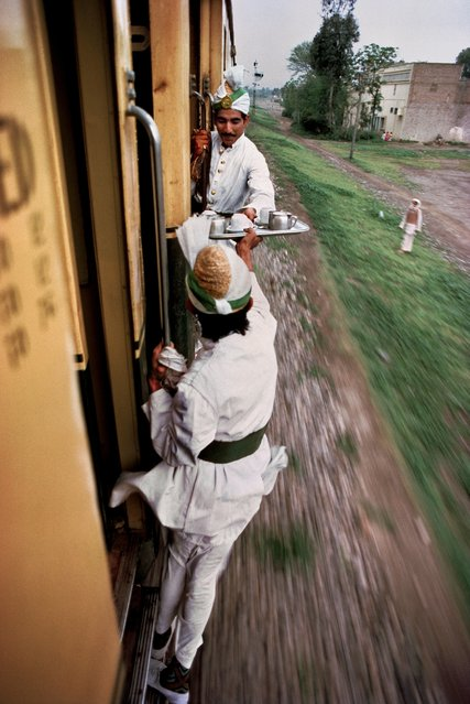 "Pakistan, 1983. Breakfast tea being passed between cars on the railway between Peshawar and Lahore. Steve McCurry writes: ""Tea is such an important part of Pakistan's culture that a tea plant is on the state emblem of the country. Tea is served with every meal, for tea breaks during the workday, and for any and every social occasion. The fleeting moment captured in this image demonstrates the integral part the nation's elixir plays in daily life, even for the travellers on this train"". (Photo by Steve McCurry/Magnum Photos)"