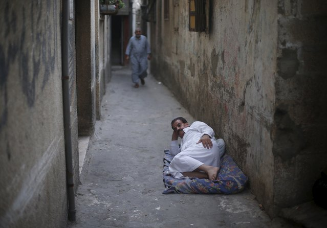 A Palestinian man lies outside his house to escape the heat during power cuts at Shatti (beach) refugee camp in Gaza City July 28, 2015. (Photo by Mohammed Salem/Reuters)