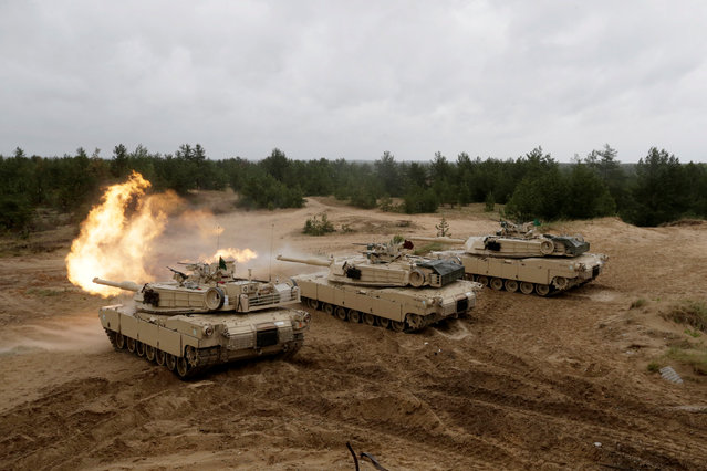 """U.S. M1 Abrams tanks fire during the """"Saber Strike"""" NATO military exercise in Adazi, Latvia, June 11, 2016. (Photo by Ints Kalnins/Reuters)"""