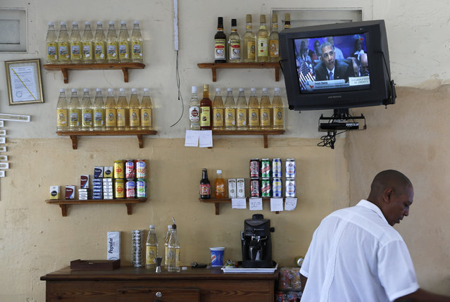A worker tends bar in Havana, Cuba, Saturday, April 11, 2015, next to a television tuned into the live telecast of President Barack Obama's speech at the VII Summit of the Americas. (Photo by Desmond Boylan/AP Photo)
