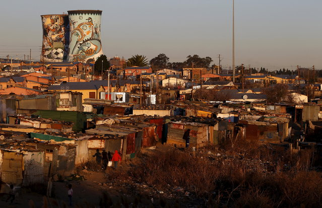 Unused cooling towers are seen overlooking an informal settlement in Soweto, South Africa, August 5, 2015. (Photo by Siphiwe Sibeko/Reuters)