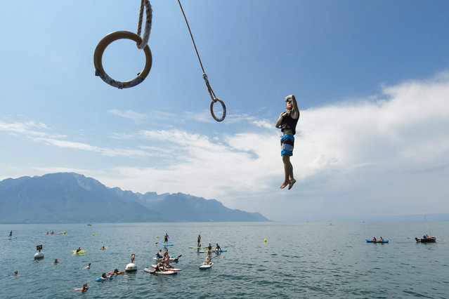 A gymnast swings on rings and then jumps into Lake Geneva at the WateRings Contest, a fun contest, in Montreux, Switzerland, 08 August 2015. (Photo by Jean-Christophe Bott/EPA)