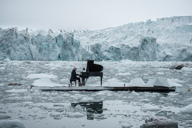"This handout picture released by Greenpeace shows Italian composer and pianist Ludovico Einaudi performing a specially composed ""Elegy for the Arctic"" on a floating platform in the Arctic Ocean on June 16, 2016 in front of the Wahlenbergbreen glacier in the archipelago Svalbard, near Ny-Alesund, Norway. With this action, Greenpeace is urging the OSPAR Commission that meets this week (20-24 June, 2016) in Tenerife, not to miss the opportunity to protect international Arctic waters under its mandate. (Photo by Pedro Armestre/AFP Photo/Greenpeace Spain)"