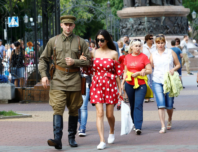 A military enthusiast dressed as World War Two Red Army officer walks with a woman as he marks the 75th anniversary of the Nazi Germany invasion, in Brest, Belarus June 21, 2016. (Photo by Vasily Fedosenko/Reuters)
