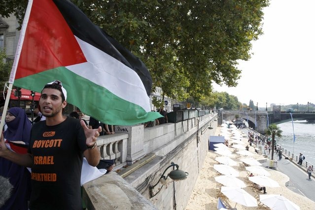 """A man wearng a T-shirt with the message, """"Boycott Israel Apartheid"""" holds a Palestinian flag during a protest action on a bridge overlooking umbrellas placed along the artificial beach along the """"Paris Plages"""" event, in Paris, France, August 13, 2015. (Photo by Pascal Rossignol/Reuters)"""
