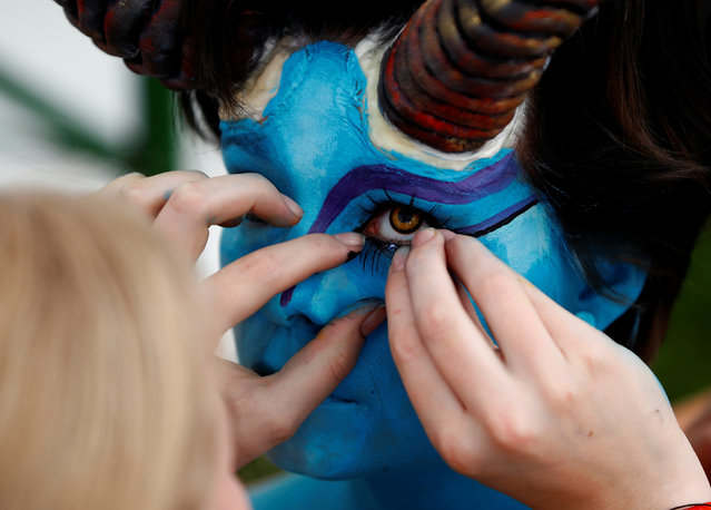 """An artist touches eye lashes on a model during the """"World Bodypainting Festival 2017"""" in Klagenfurt, Austria on July 28, 2017. (Photo by Leonhard Foeger/Reuters)"""