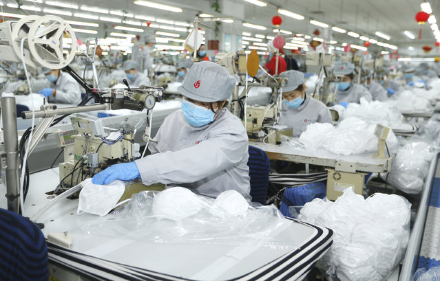 In this photo released by Xinhua News Agency, workers produce face masks in the workshop of a textile company in Jimo District of Qingdao in eastern China's Shandong Province on Wednesday, February 12, 2020. Qingdao Municipal Bureau of Industry and Information Technology has mobilized two large textile companies to produce face masks to help the fight against the novel coronavirus epidemic. (Photo by Liang Xiaopeng/Xinhua via AP Photo)