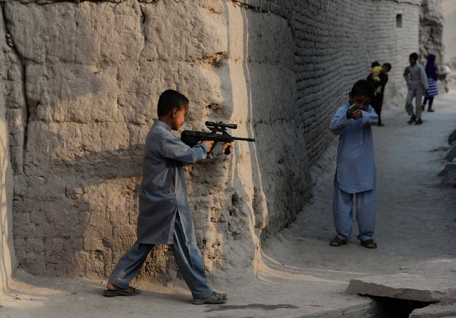 Afghan children play with plastic guns as they celebrate Eid al-Fitr and the end of the fasting month of Ramadan in Jalalabad on July 29, 2014. Muslims around the world are celebrating Eid al-Fitr this week, marking the end of the holy month of Ramadan during which followers are required to abstain from food, drink and s*x from dawn to dusk. (Photo by Noorullah Shirzada/AFP Photo)