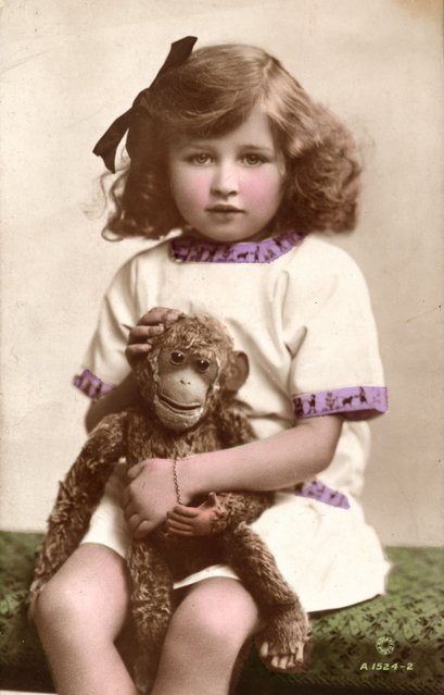 1910: Joan Cooper, daughter of British actress Gladys Cooper, with a toy monkey