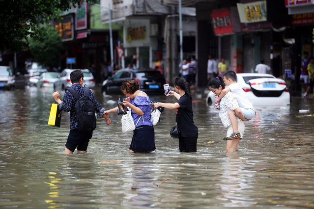 People walk through a flooded street as Typhoon Hato hits Dongguan, Guangdong province, China August 23, 2017. (Photo by Reuters/China Stringer Network)