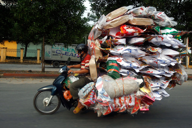 In Vietnam, a man loaded all his goods on his scooter to be able to sell during the Vu Lan Festival, on August 8, 2014. (Photo by Nguyen Huy Kham/Reuters)