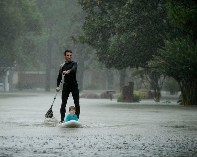 Alexendre Jorge evacuates Ethan Colman, 4, from a neighborhood inundated by floodwaters from Tropical Storm Harvey on Monday, August 28, 2017, in Houston, Texas. (Photo by Charlie Riedel/AP Photo)