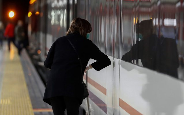 A masked commuter opens the train's doors with her elbow at a platform at Nuevos Ministerios commuter train station in Madrid, Spain, 19 March 2020. Spanish faces its fifth day of lockdown to contain the spreading of coronavirus outbreak. (Photo by Mariscal/EPA/EFE/Rex Features/Shutterstock)