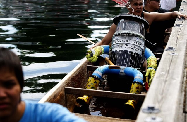 Hitchbot, Canada's hitchhiking robot, has made it's way across the country from Halifax to its final stop in Victoria, British Columbia, completing its 6,000k journey in three weeks as it arrives in a 50-foot cedar canoe with Songhees Nation members, for a traditional Coast Salish welcome at the inner harbor in Victoria, on August 18, 2014. (Photo by Chad Hipolito/The Canadian Press)