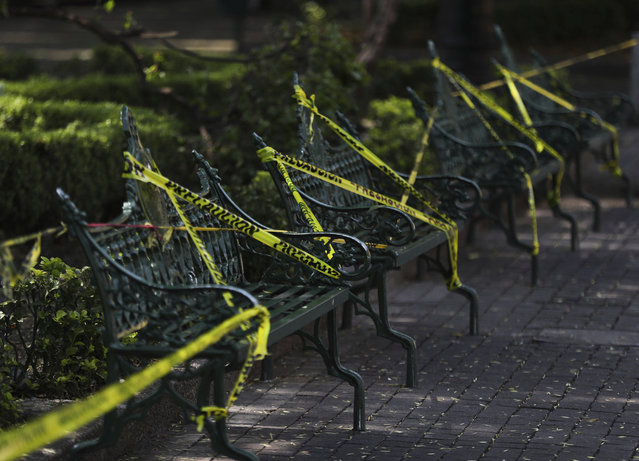 Caution tape is looped around park benches to discourage people from sitting on them in the main plaza of Coyoacan, in Mexico City, Saturday, April 4, 2020. Mexico has started taking tougher measures against the new coronavirus, but some experts warn the country is acting too late and testing too little to prevent the type of crisis unfolding across the border in the United States. (Photo by Fernando Llano/AP Photo)
