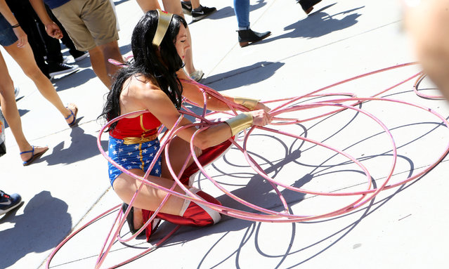 Wonder Woman gathers her hula hoops during opening day of the annual Comic-Con International in San Diego, California, United States July 21, 2016. (Photo by Rex Features/Shutterstock)