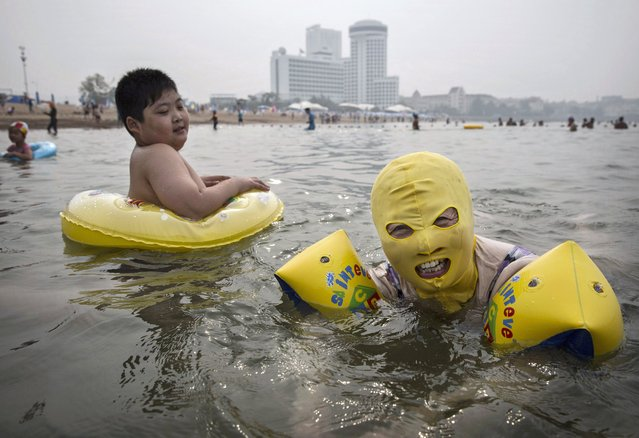 A Chinese woman wears a face-kini as she swims on August 20, 2014 on the Yellow Sea in Qingdao, China. The locally designed mask is worn by many local women to protect them from jellyfish stings, algae and the sun's ultraviolet rays. (Photo by Kevin Frayer/Getty Images)
