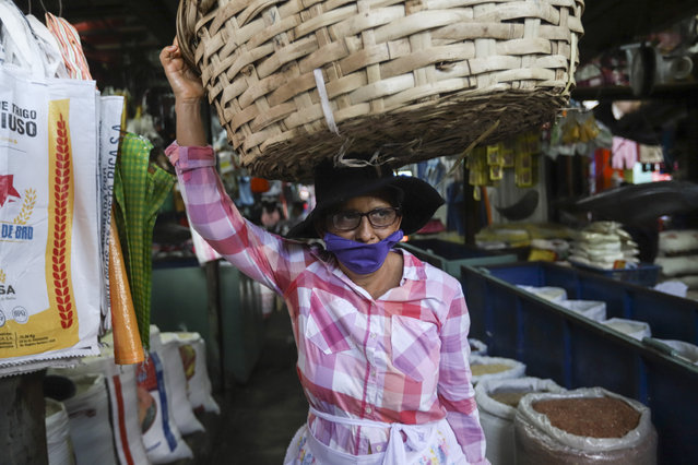 A fruit vendor, wearing a protective face mask, makes her way through a popular market in Managua, Nicaragua, Tuesday, April 7, 2020. Restaurants are empty, there's little traffic in the streets and beach tourists are sparse headed into Holy Week despite the government's encouragement for Nicaraguans to go about their normal lives. (Photo by Alfredo Zuniga/AP Photo)