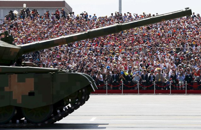 Invited guests watch and shoot footage of a passing Chinese military armored vehicle during a military parade marking the 70th Anniversary of the Victory of Chinese People's Resistance against Japanese Aggression and World Anti-Fascist War at Tiananmen Square in Beijing, China, 03 September 2015. (Photo by Rolex Dela Pena/Reuters)