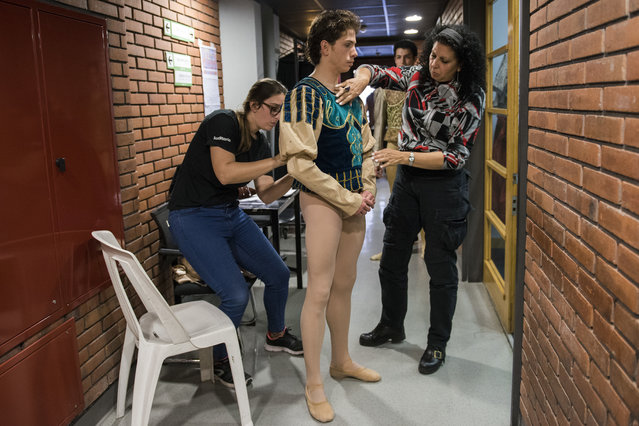In this Tuesday, September 19, 2017 photo, principal dancer Ciro Tamayo is helped by costume assistants before a dress rehearsal of Romeo and Juliet in Montevideo, Uruguay. Argentine ballet great Julio Bocca retired a decade ago after a brilliant quarter-century run but he has kept the same passion that he performed on some of the most famous stages to lift the Uruguayan company by attracting prestigious choreographers, instructors and international and local dancers. (Photo by Matilde Campodonico/AP Photo)