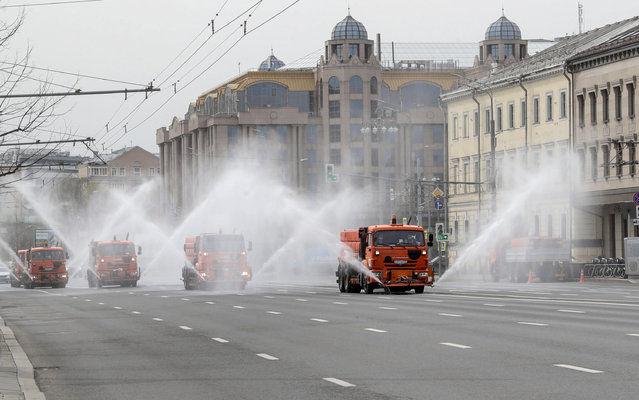 Municipal watering trucks spray disinfectant liquid on an avenue in downtown Moscow, Russia, 24 April 2020. This is the fifth mass disinfection of public spaces undertaken in Moscow so far in a bid to curb the spread of the pandemic COVID-19 disease caused by the SARS-CoV-2 coronavirus. (Photo by Sergei Chirikov/EPA/EFE/Rex Features/Shutterstock)
