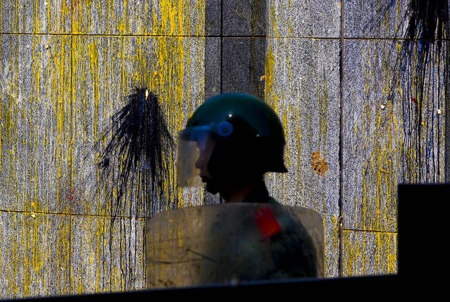 A paramilitary policeman guards an entrance of the Japanese Embassy with eggs and paint splattered on its wall, in Beijing, China, September 16, 2012 during demonstrations over islands that both nations claim are theirs. (Photo by Alexander F. Yuan/Associated Press)