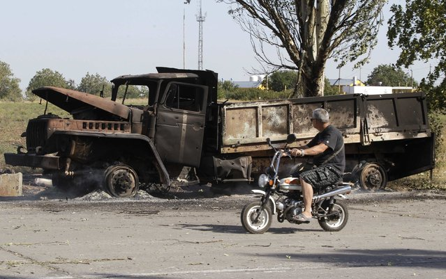 A local man rides a motorcycle past a truck burned by recent shelling on the outskirts of the southern coastal town of Mariupol September 7, 2014. Prolonged artillery fire was heard late on Saturday to the east of the port of Mariupol in eastern Ukraine, a Reuters reporter said, in what may be the first significant violation of a ceasefire declared little more than 24 hours earlier. (Photo by Vasily Fedosenko/Reuters)
