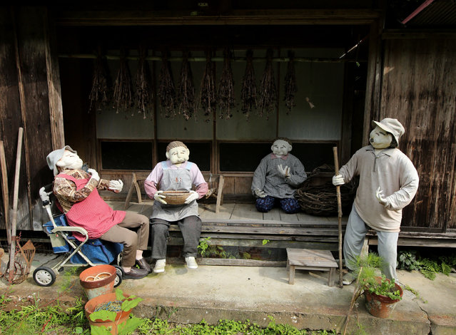 An illustration showing scarecrows resting outside of an abandoned building is on display at Kakashi no Sato, or the Scarecrow's Hometown on September 10, 2014 in Himeji, Japan. (Photo by Buddhika Weerasinghe/Getty Images)
