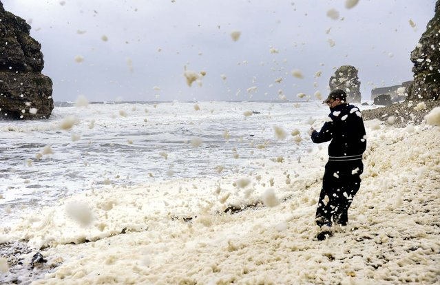 Aron Martin braves the high winds and rain on Marsden Beach , England, on September 24, 2012. Much of the country is being battered by high winds and heavy rain.  (Photo by Owen Humphreys/Associated Press)