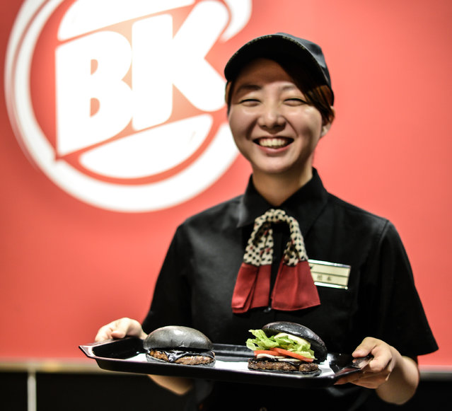 Burger King employee Minako Matsumoto displays two black hamburgers at a Burger King Japan's restaurant on September 18, 2014 in Tokyo, Japan. (Photo by Keith Tsuji/Getty Images)