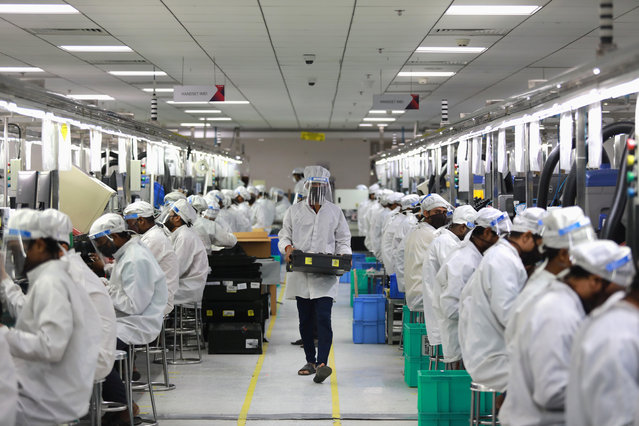 Workers wearing face shields work at an assembly line of mobile phones at Lava International Limited's manufacturing plant, after some restrictions were lifted during an extended nationwide lockdown to slow the spread of the coronavirus disease (COVID-19) in Noida, India, May 12, 2020. (Photo by Anushree Fadnavis/Reuters)