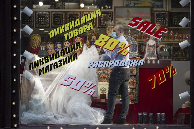 An employee removes a plastic cover from goods at the shop window after reopening in Moscow, Russia, on Monday, June 1, 2020. Monday's reopening of retail stores along with dry cleaners and repair shops comes as the pace of contagion has stabilized in the Russian capital that has accounted for about half of the nation's infections. (Photo by Alexander Zemlianichenko Jr./AP Photo)