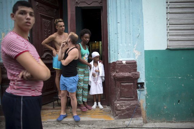 A girl dressed in white in accordance with the Afro-Cuban religion Santeria stands at her doorstep in downtown Havana, September 8, 2015. (Photo by Alexandre Meneghini/Reuters)