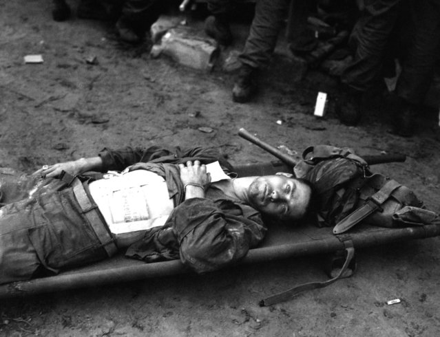 Pfc. Thomas Conlon, 21st Inf. Regt., lies on a stretcher at a medical aid station, after being wonunded while crossing the Naktong River in Korea.  September 19, 1950. (Photo by Cpl. Dennis P. Buckley)