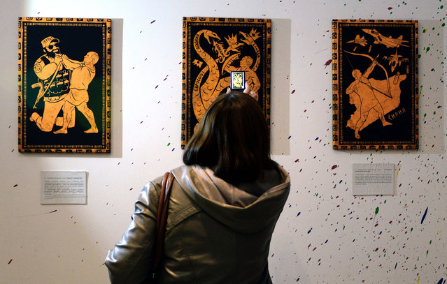 "A visitor takes photos of the paintings during the ""12 Labours of Putin"" art exhibition on October 6, 2014 marking the 60th birthday of Russia's President Vladimir Putin at the design workshop in Moscow. (Photo by Vasily Maximov/AFP Photo)"