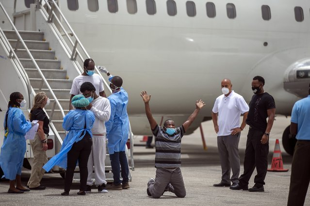 Roland Jean, a Haitian deported from the United States, kneels on the tarmac after arriving at the Toussaint Louverture airport in Port-au-Prince, Haiti, Tuesday, June 23, 2020, The man was  transported to a hotel to undergo a 14-day mandated quarantine to prevent the spread of the new coronavirus. (Photo by Dieu Nalio Chery/AP Photo)