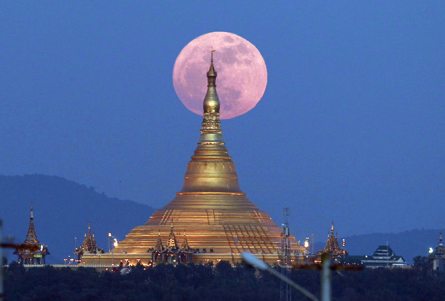 The moon rises behind the Uppatasanti Pagoda seen in Naypyitaw, Myanmar, Sunday, December 3, 2017. The Dec. 3 full moon is the first of three consecutive supermoons. The two will occur on Jan. 1 and Jan. 31, 2018. (Photo by Aung Shine Oo/AP Photo)