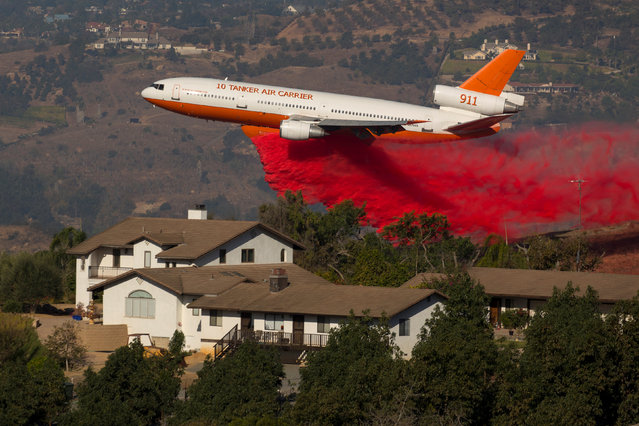 A DC-10 aircraft drops fire retardant next to a house as firefighters take advantage of light winds to attack the Lilac Fire, a fast moving wild fire in Bonsall, California, U.S., December 8, 2017. (Photo by Mike Blake/Reuters)