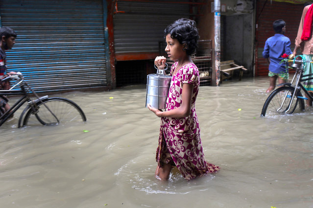 A girl wades through a waterlogged street after heavy rains caused flooding in various parts of the capital city in Dhaka, Bangladesh on July 20, 2020. (Photo by Md Rakibul Hasan/ZUMA Wire/Rex Features/Shutterstock)