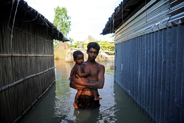 A flood-affected man stands in the water after his house got flooded in Bogura, Bangladesh on July 17, 2020. (Photo by Mohammad Ponir Hossain/Reuters)
