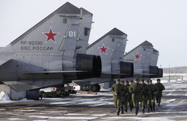 Soldiers run near a line of the Mikoyan MiG-31B supersonic interceptor aircrafts at the Kansk-Dalniy military airdrome outside the town of Kansk, 130 miles east of Russia's Siberian city of Krasnoyarsk, February 22, 2013. (Photo by Ilya Naymushin/Reuters)