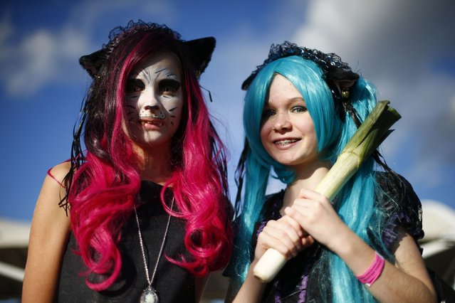 Attendees dressed as Hatsune Miku (R) and a cat person pose outside the MCM Comic Con at the Excel Centre in East London October 25, 2014. (Photo by Andrew Winning/Reuters)