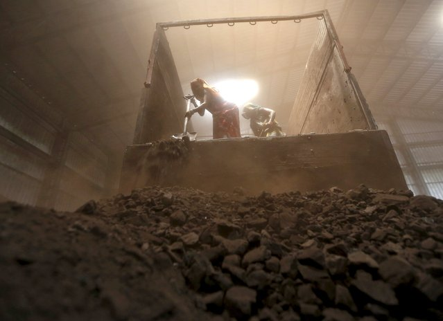 Workers unload coal from a supply truck at a yard on the outskirts of the western Indian city of Ahmedabad in this April 15, 2015 file photo. Coal futures are trading at $50 a tonne for the first time since 2003 as the commodity downturn deepens, and U.S. investment bank Goldman Sachs says the resource will never gain enough traction again to lift it out of its slump. (Photo by Amit Dave/Reuters)